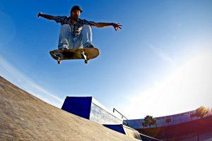 Skateboarder flying over a ramp on sunset at the local skatepark.